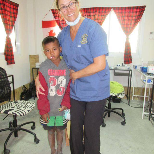 a kid and a doctor posing together after dental treatment