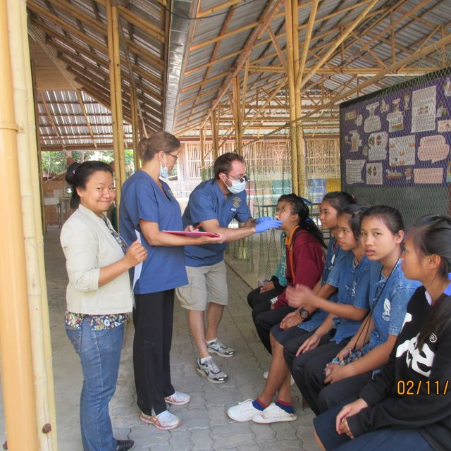 dentists checking dental health of a group of girls